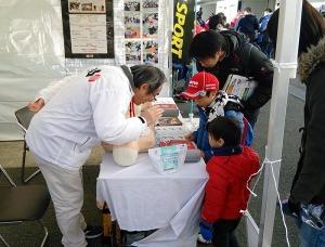 写真2:AED体験家族連れ